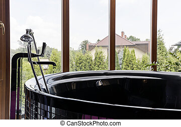 Freestanding glossy baththub with garden view - Closeup shot...