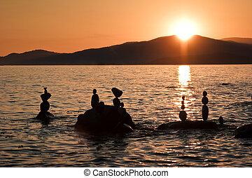 Freestanding rock sculptures in ocean at sunset