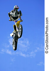 A motorcyclist is jumping in freestyle. Designs on clothings, boots, helmet and gloves have been re-arranged to hide their origins.