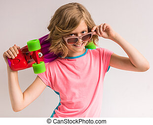 Pretty girl in sunglasses holding skateboard behind her head in studio against white background.