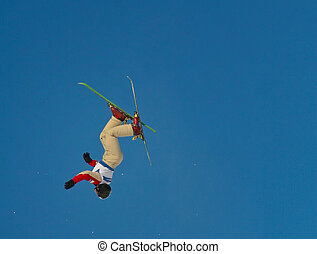 freestyle skier performing an aerial jump on a clear and sunny day