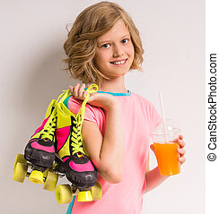 Smiling girl with roller skates on her shoulder holding glass of juice against white background.