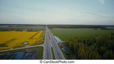Freeway in flatland with forest and canola field. Aerial...