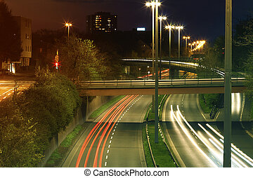 Freeway with urban night traffic with focusing on the road. Car trails on a highway