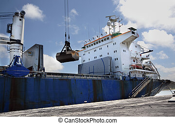 Freight-carrying - A ship charging charcoal in the port