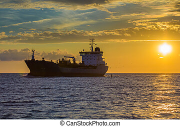 freight ship on sunset light going to port