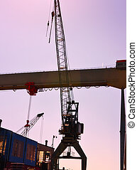 harbor cranes in the sunset