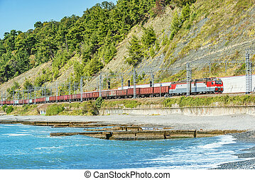 Freight train approaches to the station at morning time. Sochi.