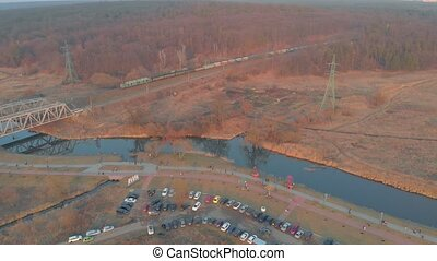 Freight train bridge river aerial drone view on sunset