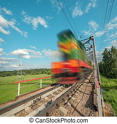 Freight train moves fast on the railway bridge.