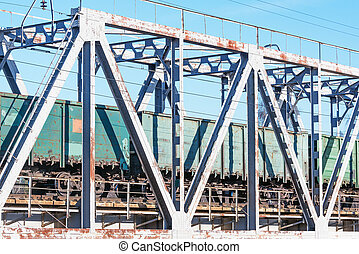 Freight train moves on the metal bridge.