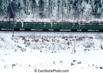 freight train moving through coniferous forest during snowfall along frozen river among hills. Northern country. Side fron top