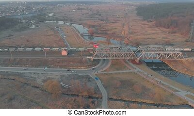 Freight train on bridge aerial drone view on sunset