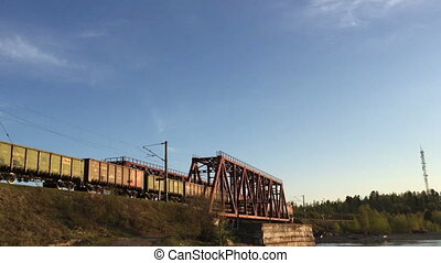 Freight train rides on rails against the blue sky