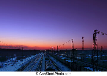 Freight trains with carriages stand on railways at winter during sunset