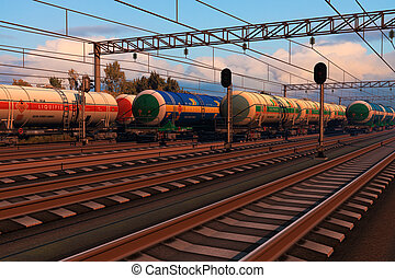 Freight trains with fuel tank cars in sunset