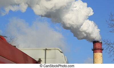 Freight transport on background of industrial smoke from the pipes against blue sky.