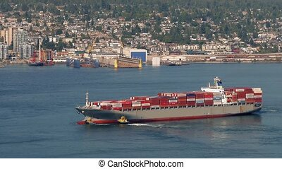Freighter Ship Turning In The Bay - Two tug boats help turn...