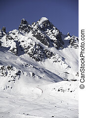 An alpine snow covered peak with ski runs and pistes