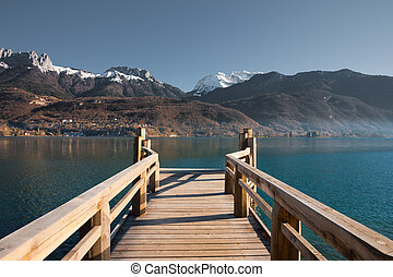 Snow capped French Alps mountains seen from a pier on Annecy Lake