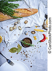 French baguette, quail eggs and rosemary herbs next to tableware. Ingredients for lunch snack on a gray background.