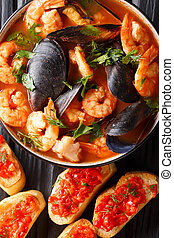 French bouillabaisse fish soup with shrimps, fish fillets and mussels closeup in a bowl. Vertical top view