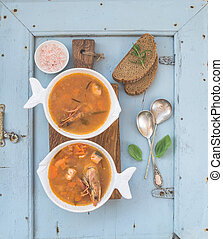 French Bouillabaisse fish tomato soup with salmon fillet, shrimp and spices on rustic wooden board over light blue background