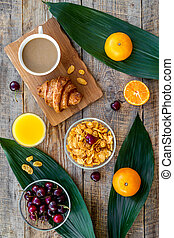 French breakfast. Fresh croissant, coffee, muesli, oranges, cherry on wooden table background top view