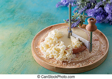 French cheese Monk Head sliced with clove petals on a wooden round surface. Bouquet of lavender.