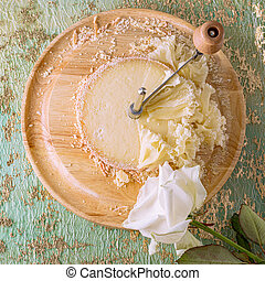 French cheese Monk Head sliced with clove petals on a wooden round surface. White rose flower.