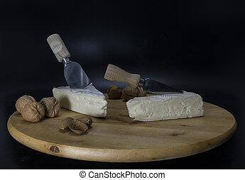 french cheese with walnnuts and wooden platter - wooden...