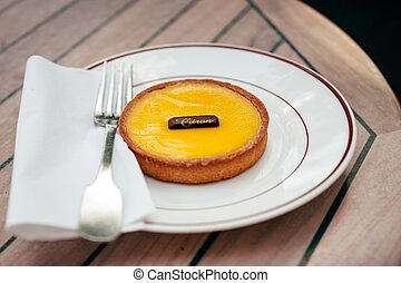 Delicious tarte au citron (lemon tart) on plate in a Parisian cafe. Tilt-shift lens used for better image