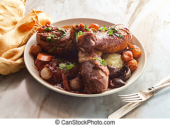 French cuisine Coq Au Vin stew with crimini mushrooms pearl onions and carrots in a red wine brandy sauce served over mashed potatoes