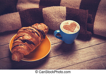 french croissant and cup of coffee on a wooden table
