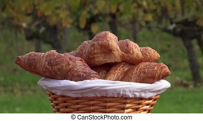 French croissants in a basket - rotating basket with...