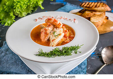 French fish soup Bouillabaisse with seafood, salmon fillet, shrimp, rich flavor, delicious dinner in a white beautiful plate