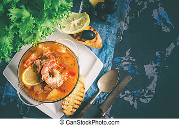 French fish soup Bouillabaisse with seafood, salmon fillet, shrimp, rich flavor, delicious dinner in a white beautiful plate. spase