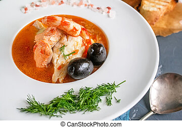 French fish soup Bouillabaisse with seafood, salmon fillet, shrimp, rich flavor, delicious dinner in a white beautiful plate. Close up