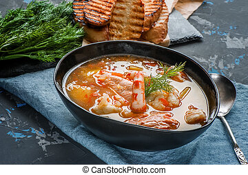 French fish soup Bouillabaisse with seafood, salmon fillet, shrimp, rich flavor, delicious dinner. Close up