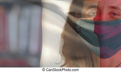 Animation of French flag waving over portrait of a Caucasian woman wearing face mask protecting against Covid 19 coronavirus. Global coronavirus pandemic concept digitally generated image.
