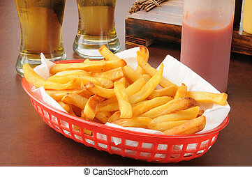 French fries and beer - A basket of french fries and two...