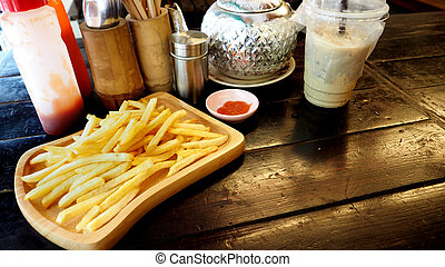 French fries and coffee on wood desk in shop