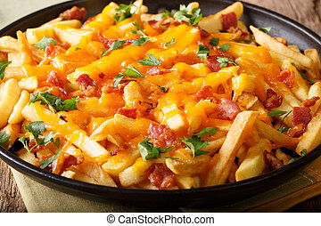 French fries baked with cheddar cheese, bacon and parsley closeup. horizontal