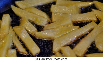 French fries cooking in boiling oil.