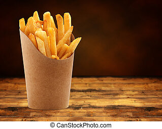 fries - french fries in a paper basket on wooden table