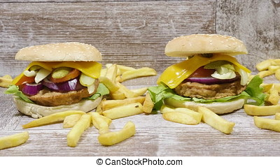 French fries lying on wooden background next to delicious burgers