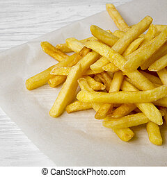 French fries on a white wooden background, side view. Close-up.