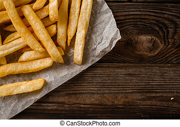 French fries on wooden table.