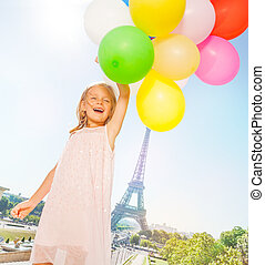French little girl flies with balloons bouquet
