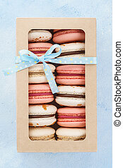 French macarons in a gift box with ribbon on blue background.